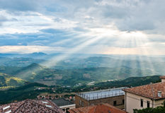 Sun rays shining down on hills Stock Images