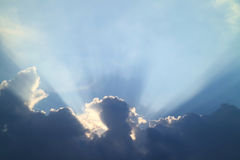 Sun rays shining through the gray clouds on blue sky Royalty Free Stock Photos