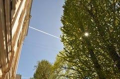 Sun rays sky color house. tree flight. Flying plane on a bright blue sky draws the flight path like chalk on a blackboard Royalty Free Stock Photo