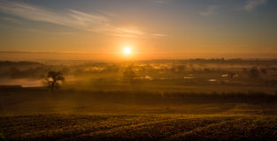 Sun rays spreading across miles of misty countryside Royalty Free Stock Images