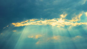 Sun rays stream through clouds. In bright, blue sky at sunset. 4K Timelapse stock footage shot stock video footage