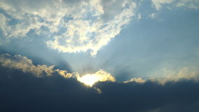 Sun rays stream through clouds. In bright, blue sky at sunset. 4K Timelapse stock footage shot stock footage