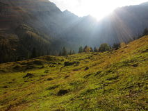 Sun rays streaming into alpine valley at fall Stock Photos