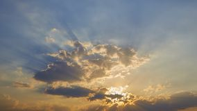 Sun rays are striking through the clouds. Sunset with striking rays of sunlight. God radiation concept royalty free stock photo