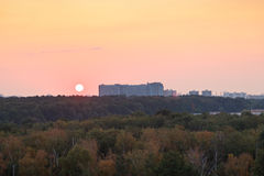 Sun during red sunrise over houses and urban park Stock Photography