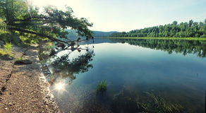 Sun reflecting in the shallow waters of a quiet river Stock Image