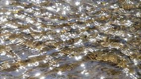 Sun reflections on flowing water over stones stock footage