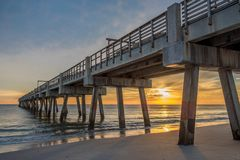 Sun reflections in the ocean at Jacksonville Beach Pier. The sun breaks through the clouds to cast reflections on the ocean water just as the sun comes up Stock Image