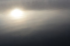 Sun reflects in misty pond. Reflection of the sun in a misty lake Stock Photo