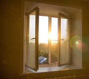 Sun rise behind the window blinds and curtains shades. For background stock photo