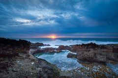 Sun rise over rocky coastline Stock Photo