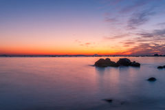Sun rise at rock sea beach. Golden reflection on water and red sky before the sun rising Stock Photo