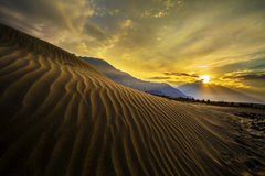 Sun rise at sand dunes against the background of distant colorful mountain range and sunrise sky, Ladakh, Himalaya, Jammu & Kashmi Stock Image