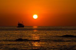 Sun rise from the sea and fisherman boat Royalty Free Stock Image