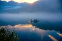 A fishman cast a net on the boat in the fog on the river, the golden cloud reflection on the surface of water, at dawn. The sun rise up and shine on cloud, a royalty free stock photography
