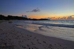 Sun Rise on a Wide Sandy Beach. A sweeping beach, with the waves lapping the shore, as the sun rises on the horizon Stock Photography