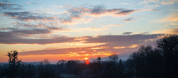 The sun rises behind clouds Royalty Free Stock Images