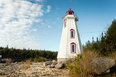The Big Tub lighthouse in Tobermory, Ontario. The sun rises behind high cloud at Big Tub lighthouse in Tobermory, Ontario royalty free stock photo