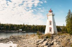 Lighthouse overlooking Big Tub Harbour, Tobermory, Ontario. The sun rises behind high cloud at Big Tub lighthouse in Tobermory, Ontario royalty free stock images