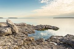 Sunrise at Big Tub Point, Tobermory, Ontario. The sun rises behind high cloud at Big Tub Point, Tobermory, Ontario stock images