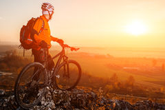Sun rises behind man getting ready to ride his road bike on lonely paved highway during summer. Includes copy space. Stock Image