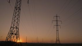 The Sun Rises from Beyond Horizon and Shines Through High Voltage Transmission Pedestal. At Sunrise stock video footage