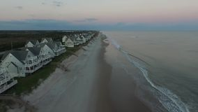 The sun rises on first row oceanfront beach Houses, North Topsail Island Pier, North Topsail Beach, NC stock video footage