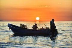 Song of the fisherman. The sun rises, and the fishermen are fishing in the sea to form a harmonious song Stock Photo