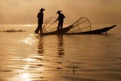 Sun rises on fishermen silhouettes Royalty Free Stock Photos