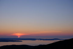 The sun rises over the horizon and lights up the bay outside of Royalty Free Stock Photos