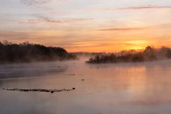 The sun rises over the river, wrapped in a gray mist. stock image