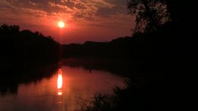 The sun rises over the Wild River. Dawn over the river Khoper, Russia. The sun has just appeared from behind the trees and its disc is reflected in the water stock footage