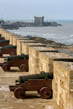 The sun rises overa row of canons at the former fortress at Essaouira in Morocco. Stock Photo