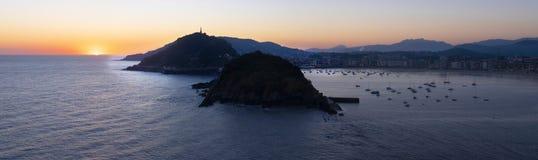 The sun rises in the sea. City of San Sebastian royalty free stock image
