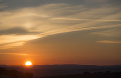 Sun rising. Orange sun rising over horizon with mountains with clouds stock photo