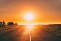 Free Sun Rising Above Asphalt Country Open Road In Sunny Sunrise Morning. Open Road In Summer Or Autumn Season At Sunny Royalty Free Stock Photo - 162278735