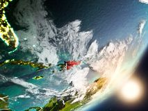 Sun rising above Dominican Republic from space. Dominican Republic from space with highly detailed surface textures and visible country borders. 3D illustration Royalty Free Stock Photo