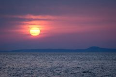 Sun rising above Kuril Islands, Russia, wallpaper, view from Hokkaido, Japan, Beautiful morning sunrise scene, sun above calm ocea. N,romantic mystic scene from stock image