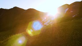 Sun rising from behind snow mountains. Tight shot with a beautiful lens flare moves through frame stock footage
