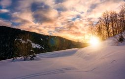 Sun rising behind the snowy slope. Wonderful nature winter scenery in mountainous area Royalty Free Stock Photo