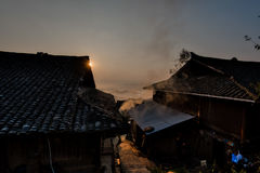 Sun rising behingtraditional Chinese minority houses Royalty Free Stock Photos