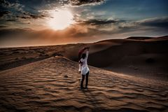 A Girl Dancing in the Desert Dunes. The sun rising on the desert dunes drawing beautiful patterns on the sand while a beautiful girl dances, Kashan,Iran stock image