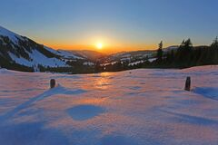 Sun Rising in Horizon over Snow Coated Mountains Royalty Free Stock Images