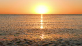 Sun Rising Over the Calm Sea. Tranquil scene, waves running towards the camera during morning sunrise on caribbean Beach, slightly bigger waves stock footage