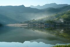 Lake Reflecion in Summer Morning. The sun is rising over the hill by the lake r. It`s very beautiful and quiet. It`s a good place to camping,hiking,fishing Stock Image