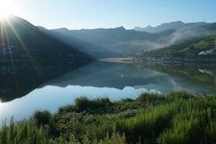 Lake Reflecion in Summer Morning. The sun is rising over the hill by the lake r. It`s very beautiful and quiet. It`s a good place to camping,hiking,fishing Stock Photo