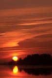 Sun rising over lake Stock Photo