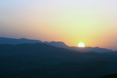 Sun rising over the mountains. A picture of the blazing red sun, rising over the silhouette of a mountain range stock photo