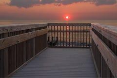 Sun rising over a railing at the beach stock photos