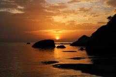 Sun rising over rocks in the ocean Stock Photos